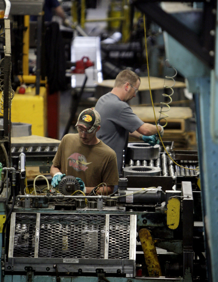 FILE - In this June 3, 2009 file photo, Baldor Electric Co. employees Dave Johnston, left, and Steve Davis, right, work inside the company\'s factory in St. Louis. The government issues its second of three estimates of how fast the U.S. economy grew in the January-March quarter later Thursday May 29, 2014. (AP Photo/Jeff Roberson, File)