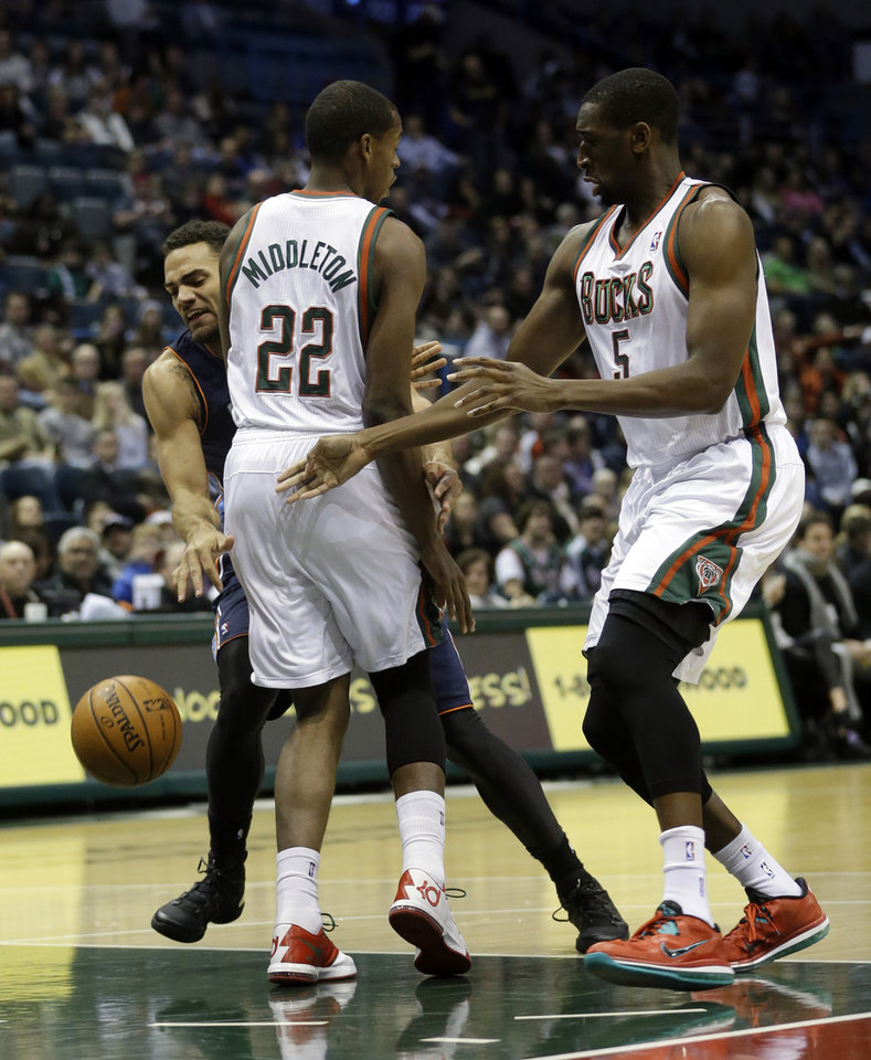 Photo - Charlotte Bobcats' Jeff Taylor loses the ball as he runs into Milwaukee Bucks' Khris Middleton (22) and Ekpe Udoh (5) during the first half of an NBA basketball game on Saturday, Nov. 23, 2013, in Milwaukee. (AP Photo/Morry Gash)