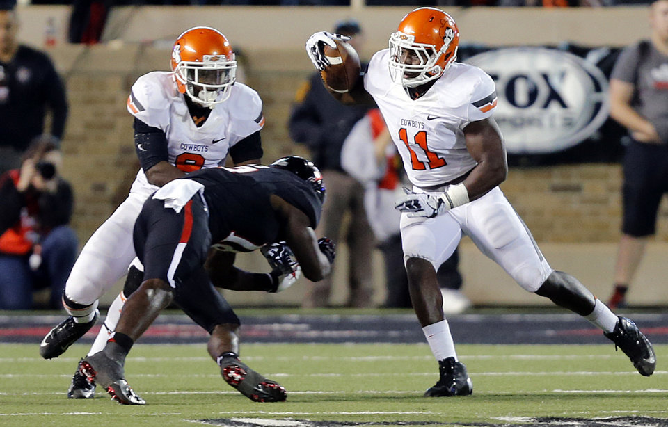 Oklahoma State 's Shaun Lewis (11) returns an interception past Jeremiah Tshimanga (9) and Texas Tech's Eric Ward (18) during the college football game between the Oklahoma State University Cowboys (OSU) and the Texas Tech University Red Raiders (TTU) at Jones AT&T Stadium in Lubbock, Tex. on Saturday, Nov. 2, 2013.  Photo by Chris Landsberger, The Oklahoman