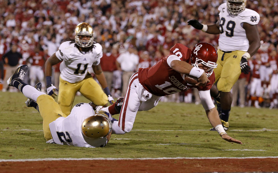 Photo - OU's Blake Bell (10) scores a touchdown past Notre Dame's Bennett Jackson (2) during the college football game between the University of Oklahoma Sooners (OU) and the Notre Dame Fighting Irish at Gaylord Family-Oklahoma Memorial Stadium in Norman, Okla., Saturday, Oct. 27, 2012. Oklahoma lost 30-13. Photo by Bryan Terry, The Oklahoman