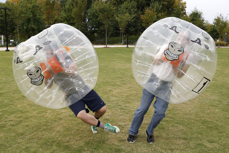Photo - Oklahoman writer Adam Kemp and an opponent bounce off of each other during a BubbleBall soccer match at the Myriad Gardens in Oklahoma City, OK, Friday, October 16, 2015,  Photo by Paul Hellstern, The Oklahoman