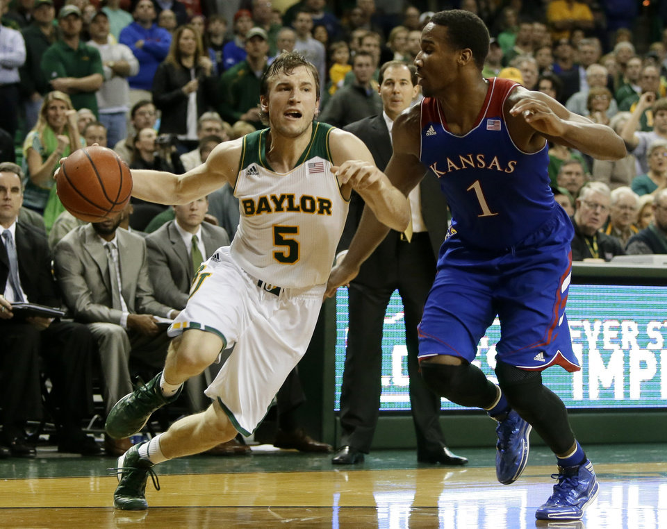Photo - Baylor guard Brady Heslip (5) attempts to get by Kansas' Wayne Selden, Jr. (1) on a drive to the basket in the second half of an NCAA college basketball game, Tuesday, Feb. 4, 2014, in Waco, Texas. Kansas won 69-52.  (AP Photo/Tony Gutierrez)