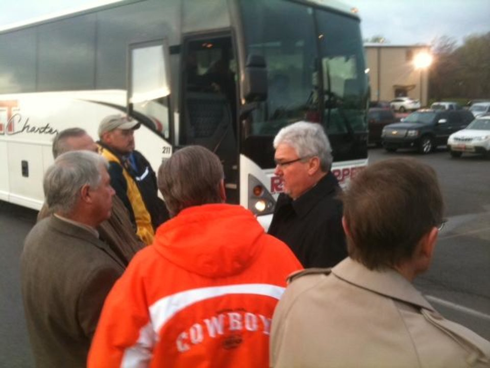People wait to board buses in the parking lot of Ripley High School to travel to site where the president will speak Thursday. About 100 people here by invitation are boarding buses. Photo by Jim Beckel, The Oklahoman