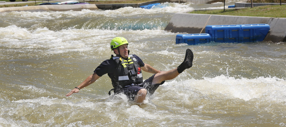 Photo -  Lt. Josh Pearcy jumps into the water as Oklahoma City Fire Station 8 practices swift-water rescue techniques at Riversport Rapids. Fire Station 8 houses Oklahoma City's urban and water rescue teams in the Stockyards District. [Photo By Steve Gooch, The Oklahoman]