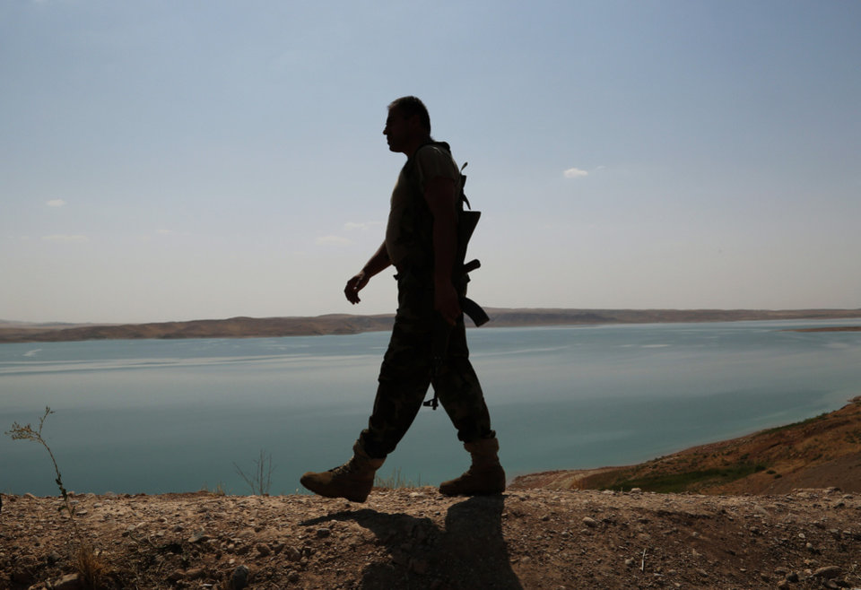 Photo - A Kurdish peshmerga fighter patrols near the Mosul Dam at the town of Chamibarakat outside Mosul, Iraq, Sunday, Aug. 17, 2014. Kurdish forces took over parts of the largest dam in Iraq on Sunday less than two weeks after it was captured by the Islamic State extremist group, Kurdish security officials said, as U.S. and Iraqi planes aided their advance by bombing militant targets near the facility. (AP Photo/Khalid Mohammed)
