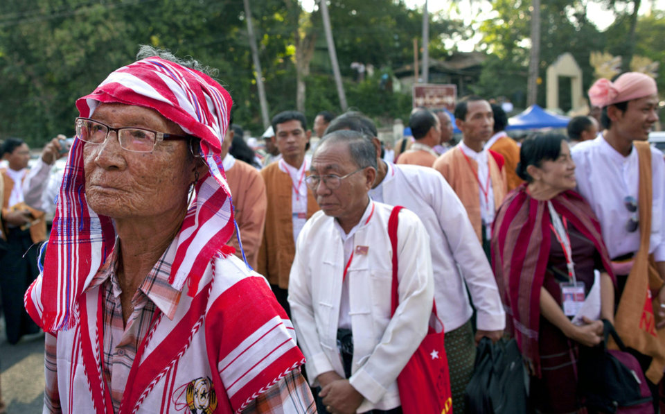 "Photo - A Karen ethnic minority representative of Aung San Suu Kyi's National League for Democracy, left, stands in a line to participate in first ever NLD party congress in Yangon, Myanmar, Friday, March 8, 2013. Nearly 900 representatives from across the country stood in neat lines outside the Taw Win (""Royal Rose"") restaurant, waiting to be screened for entry to elect their party leadership for the first time in the NLD's 25-year history. (AP Photo/Gemunu Amarasinghe)"