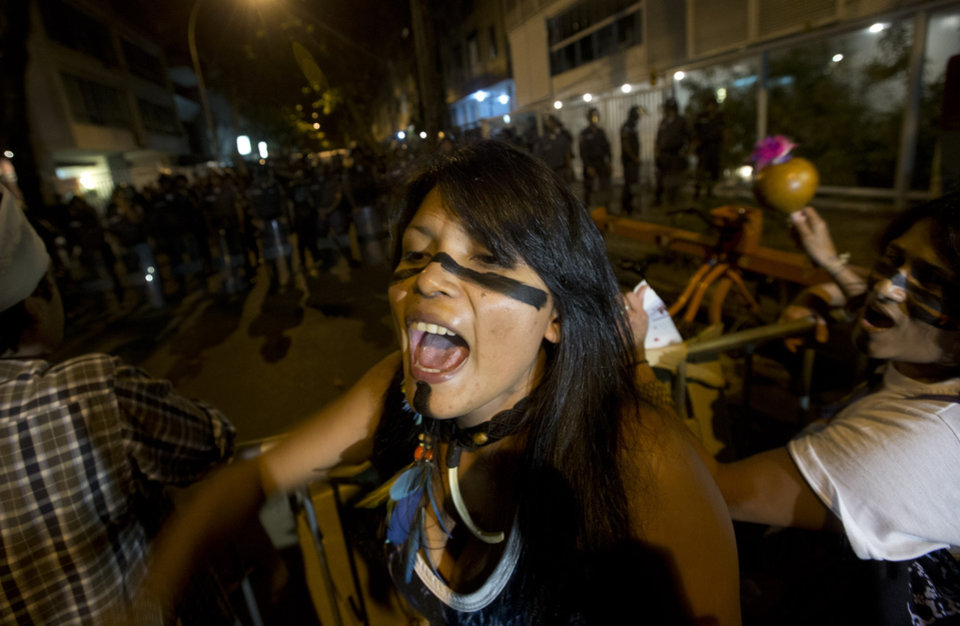 Photo - An indigenous woman shouts slogans against Rio de Janeiro's Gov. Sergio Cabral during a protest near his home, in Rio de Janeiro, Brazil, Wednesday, July 17, 2013. The demonstrators are demanding better public transit, health and education services. (AP Photo/Silvia Izquierdo)