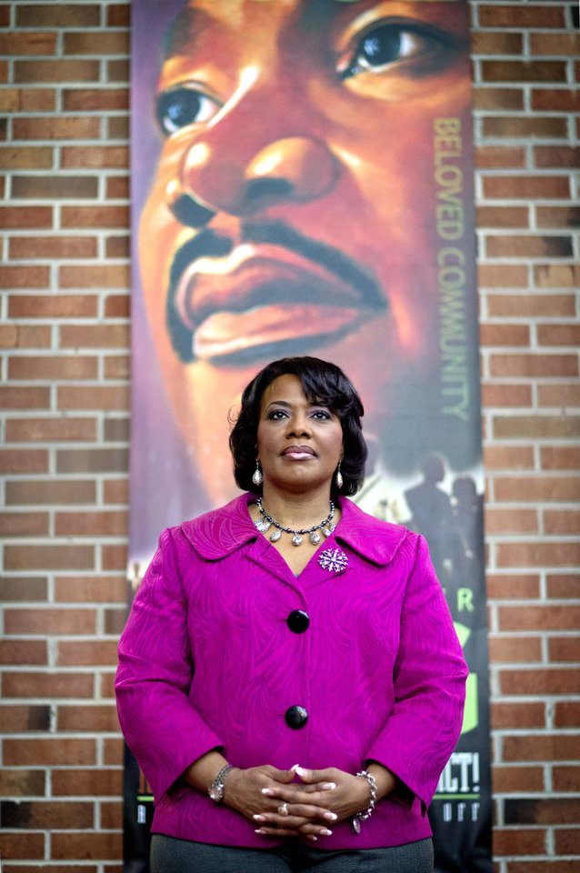 Photo - In this Tuesday, Jan. 8, 2013 photo, Bernice King stands in the King Center next to a banner hanging in memory of her father, Dr. Martin Luther King Jr., in Atlanta. The legacy of the civil rights movement has long been invoked when people talk about the nation's first black president, and this year the memory of the Rev. Martin Luther King Jr. and the life of President Barack Obama will overlap significantly for a day. For only the second time, the presidential inauguration falls on the Rev. Martin Luther King Jr. holiday. (AP Photo/David Goldman)