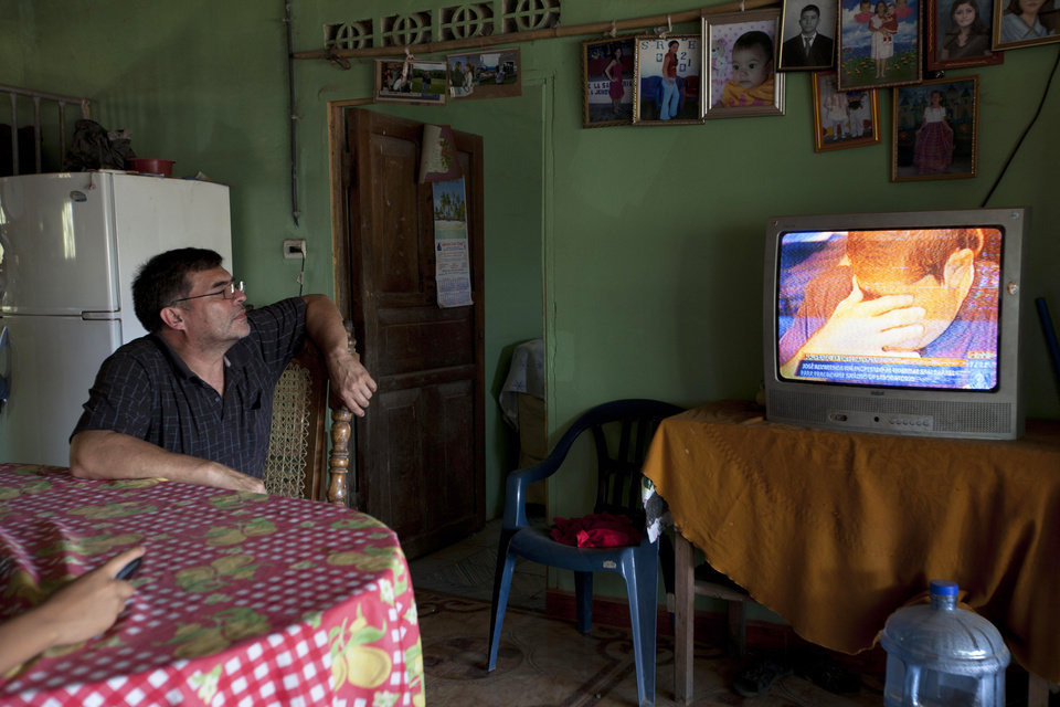 Photo - Jose Alvarenga watches his cousin Jose Salvador Alvarenga on the local news channel, reacting as he returns to his native country, from their family home in Garita Palmera, El Salvador, Wednesday, Feb. 12, 2014. The family of Alvarenga, the 37-year-old who says he survived more than a year on a small boat drifting from Mexico across the Pacific Ocean to the Marshall Islands, is preparing for his return to his home town after he landed in the capital late Tuesday. (AP Photo/Moises Castillo)