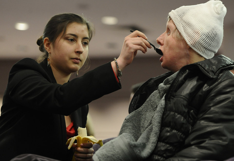 Photo - Charla Nash, right, eats a banana with help from her daughter Briana Nash during a public hearing with Connecticut legislators at the Legislative Office Building, Friday, March 21, 2014, in Hartford, Conn. Nash who was mauled by a friend's chimpanzee in 2009 is making a personal plea to allow her to sue the state for $150 million in damages. The panel is considering a bill that would override the June decision by the State Claims Commissioner, who dismissed Nash's initial request for permission to sue. The state generally is immune from lawsuits, unless allowed by the claims commissioner. (AP Photo/Jessica Hill)