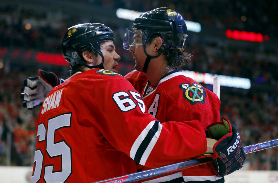Photo - Chicago Blackhawks center Andrew Shaw (65) celebrates with left wing Patrick Sharp (10) after Sharp scored a goal against the Carolina Hurricanes during the second period of an NHL hockey game in Chicago, Friday, March 21, 2014. (AP Photo/Jeff Haynes)