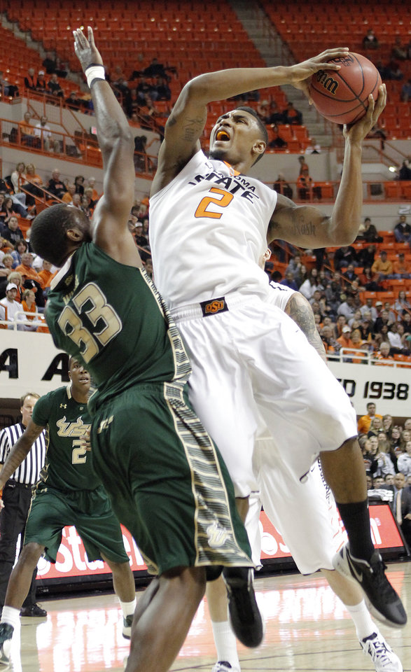 Oklahoma State 's Le'Bryan Nash (2) drives against South Florida Bulls' Kore White (33) during the college basketball game between Oklahoma State University (OSU) and the University of South Florida (USF) on Wednesday , Dec. 5, 2012, in Stillwater, Okla.   Photo by Chris Landsberger, The Oklahoman