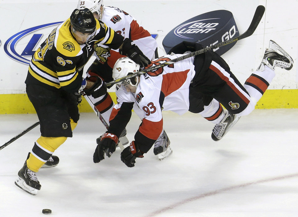Photo - Boston Bruins left wing Brad Marchand (63), left, collides with Ottawa Senators center Mika Zibanejad (93), right, of Sweden, in the first period of an NHL hockey game in Boston, Sunday, April 28, 2013. Senators left wing Jakob Silfverberg, background, skates behind. (AP Photo/Steven Senne)