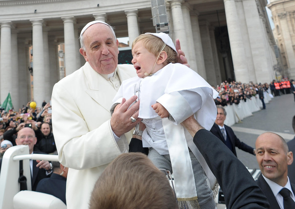 Photo - In this picture provided by the Vatican newspaper L'Osservatore Romano, 19-month-old Daniele De Sanctis, dressed up as a pope, is handed to Pope Francis as he is driven through the crowd during his weekly general audience in St. Peter's Square at the Vatican, Wednesday, Feb. 26, 2014. Francis kissed the child as the new must-have Carnival costume made its debut at the pope's general audience Wednesday. During Carnival in Italy, children often go to school and spend their weekends dressed up in pirate, princess — and now pope — costumes. Carnival, also known as mardi gras, marks the period before the church's solemn Lenten season begins. Daniele's mother, Paola Ciabattini, said she dressed her son as a pope in a demonstration of affection towards Pope Francis. (AP Photo/L'Osservatore Romano, ho)