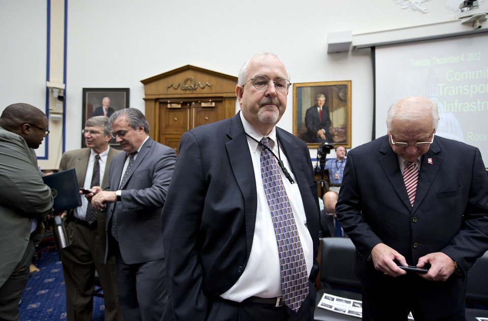 Federal Emergency Management Agency Administrator Craig Fugate, center, arrives on Capitol Hill in Washington, Tuesday, Dec. 4, 2012, to testify before the House Transportation and Infrastructure Committee hearing on the preparedness and response to Hurricane Sandy. At right is Robert Latham Jr., executive director of the Mississippi Emergency Management Agency, who was to testify.  (AP Photo/J. Scott Applewhite)