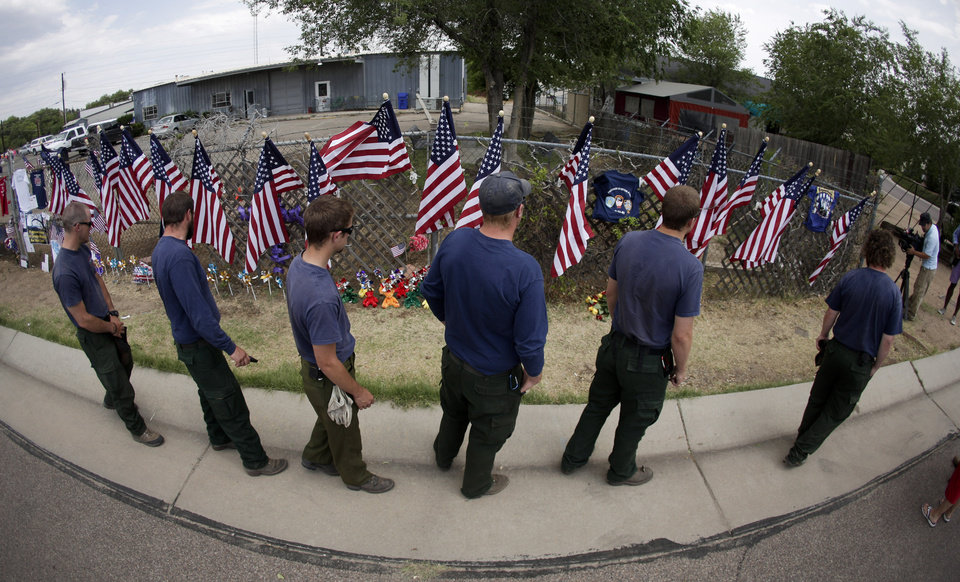 Photo - Members of the Centennial Initial Attack Fire Crew, from Island Park, Idaho, pay their respects at a memorial outside the Granite Mountain Interagency Hotshot Crew fire station, Thursday, July 4, 2013, in Prescott, Ariz. Nineteen firefighters from Granite Mountain Interagency Hotshot Crew were killed battling a wildfire near Yarnell, Ariz., Sunday. The elite crew of firefighters were overtaken by the out-of-control blaze as they tried to protect themselves from the flames under fire-resistant shields. (AP Photo/Chris Carlson)