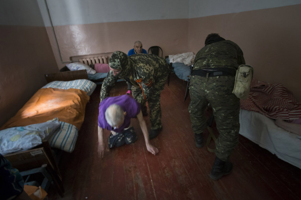 Photo - Pro-Russian armed militants assist patients of a psychiatric hospital in Slovyansk, eastern Ukraine, on Sunday, May 25 2014. The hospital was badly damaged in an artillery shelling late Saturday and patients had to be evacuated. The rebels, who have fought government forces in the area in weeks of intense clashes, helped patients to get from the hospital's basement to a section that wasn't ruined by the shelling. (AP Photo/Alexander Zemlianichenko)