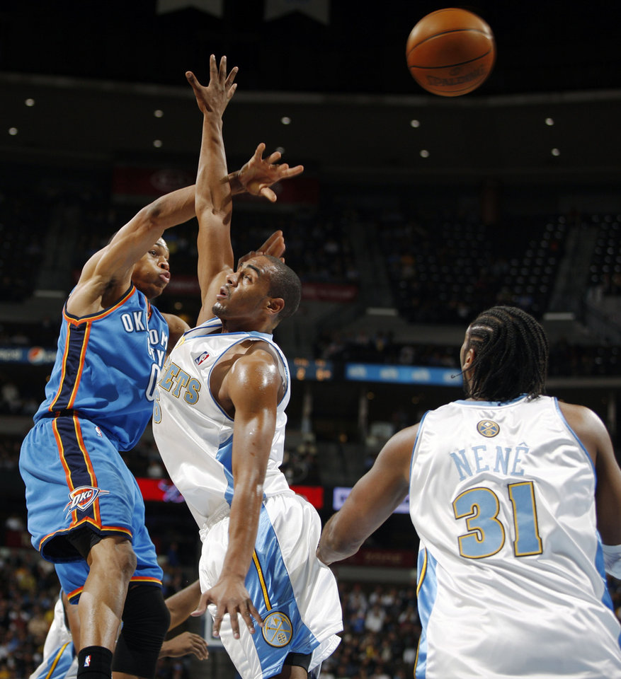 Photo - Oklahoma City Thunder guard Russell Westbrook, left, loses control of the ball as he goes up for a shot as Denver Nuggets guard Arron Afflalo, center, and forward Nene, of Brazil, cover in the first quarter of an NBA basketball game in Denver on Monday, Dec. 14, 2009. (AP Photo/David Zalubowski) ORG XMIT: CODZ102