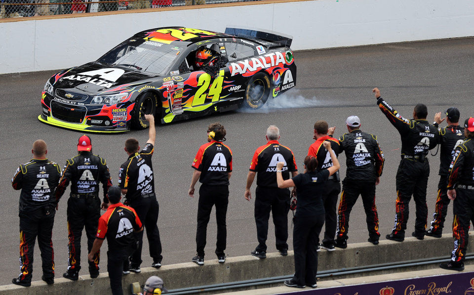 Photo - Jeff Gordon celebrates in front of his crew after winning the NASCAR Brickyard 400 auto race at Indianapolis Motor Speedway in Indianapolis, Sunday, July 27, 2014.  (AP Photo/Dave Parker)