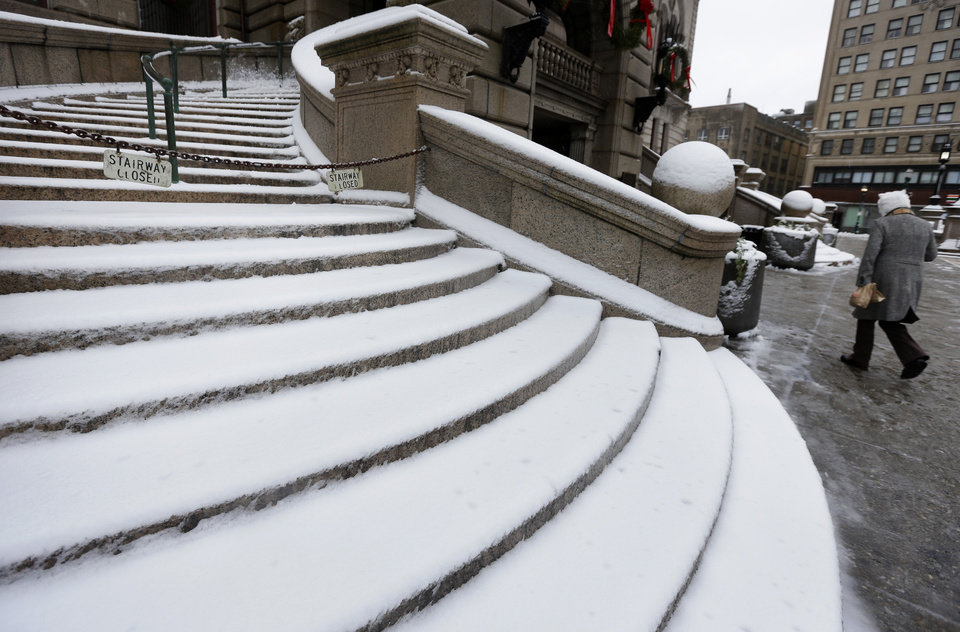 A passer-by walks past a snow-covered stairway at Worcester City Hall, in Worcester, Mass., Thursday, Dec. 27, 2012.  Areas in the north and west of the state have received a blanket of heavy, wet snow. (AP Photo/Steven Senne)