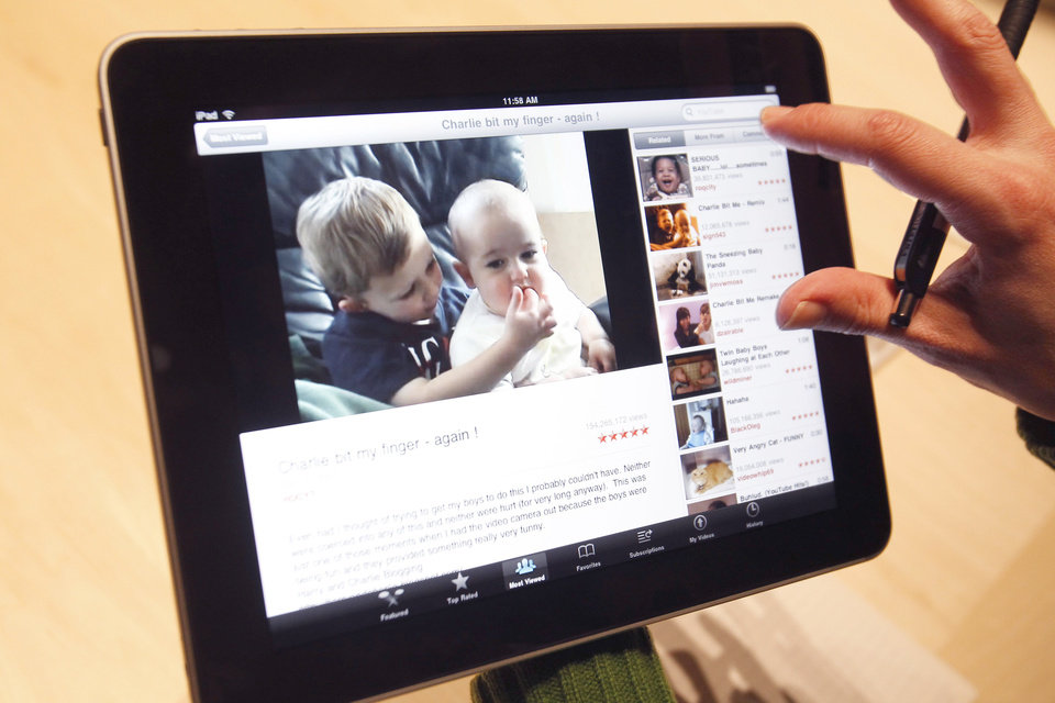 Photo - The Apple iPad is examined after its unveiling at the Moscone Center in San Francisco. AP File Photo