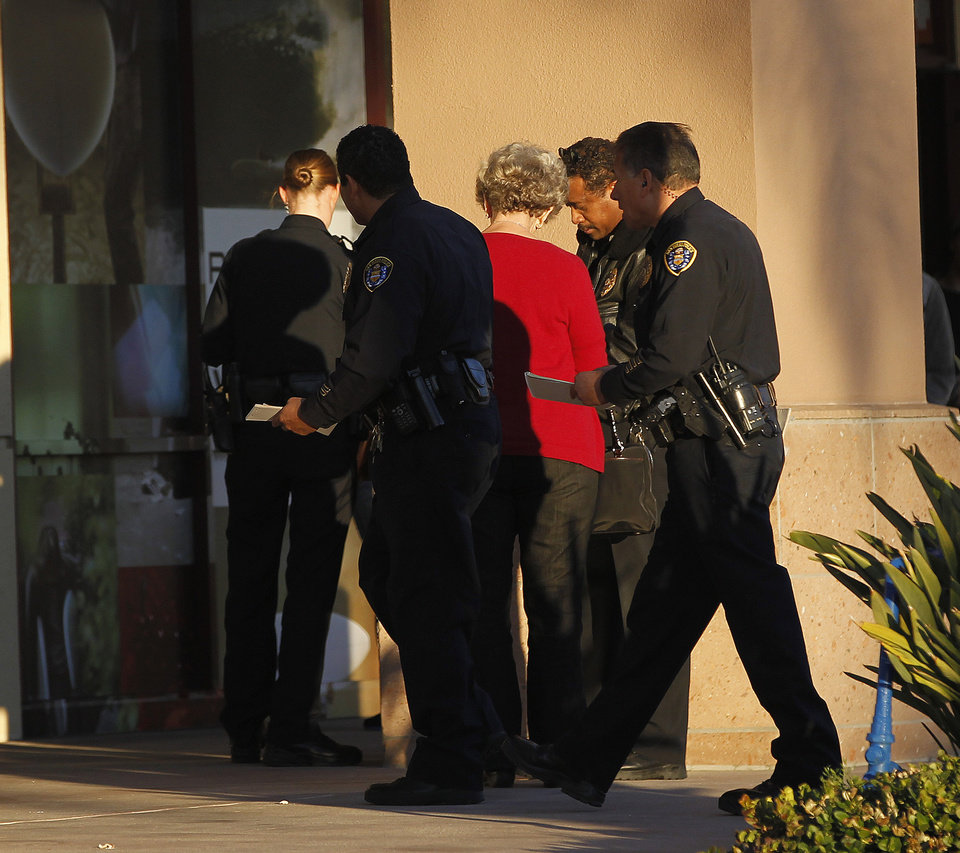 Photo - Police officers talk with a witness near a shooting at the Reading Cinemas in San Diego on Saturday evening, Jan. 12, 2013. Police shot and critically wounded a man suspected of chasing his girlfriend with a handgun after they found him hiding inside the movie theater. It was the second shooting at a San Diego County movie theater in as many days. (AP Photo/UT San Diego, Earnie Grafton)