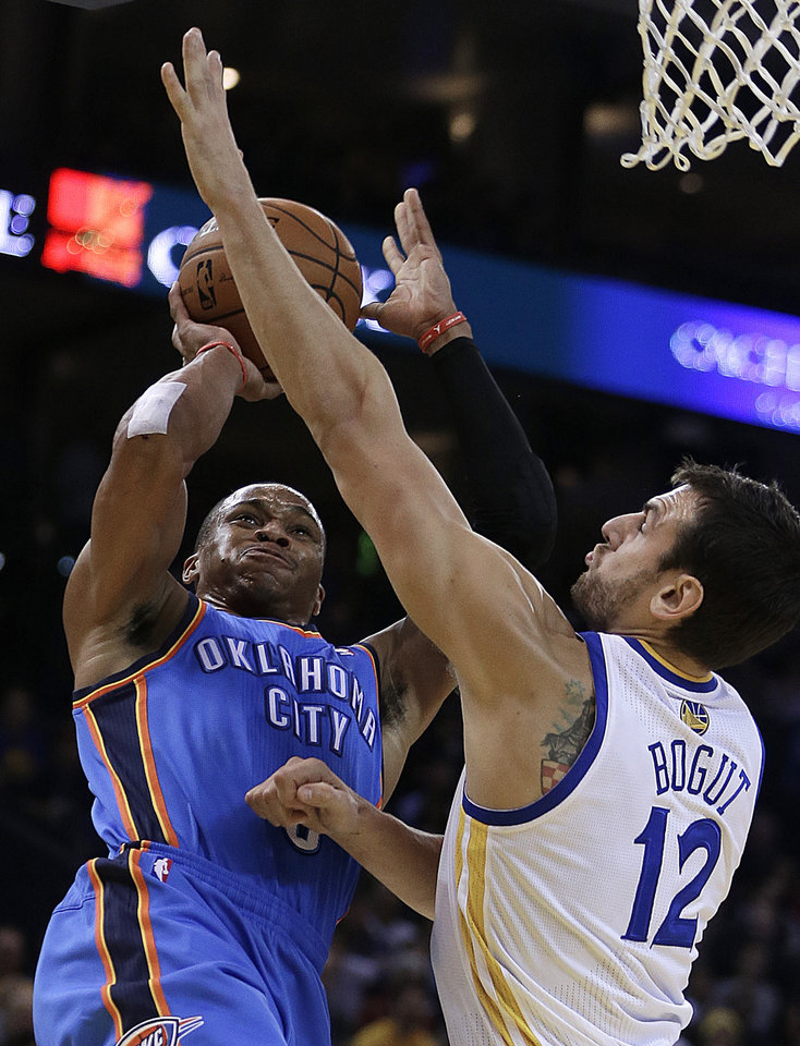 Oklahoma City Thunder's Russell Westbrook, left, shoots against Golden State Warriors' Andrew Bogut (12) during the first half of an NBA basketball game Thursday, Nov. 14, 2013, in Oakland, Calif. (AP Photo/Ben Margot)