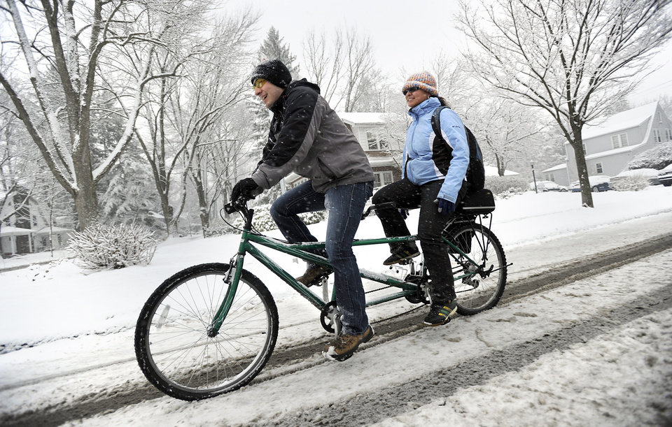 Penn State students David Leinbach and Samantha Rosado ride a tandem bicycle to campus along N Allen Street, in State College, Pa., Monday, March 25, 2013. Heavy snow fell throughout Centre County, Monday, causing local schools to be closed and hazardous traveling conditions.  (AP Photo/Centre Daily Times, Nabil K. Mark) MANDATORY CREDIT; MAGS OUT
