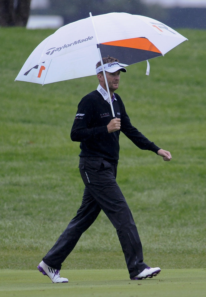 Photo - David Lynn walks the first fairway under an umbrella as rain falls during the final round of the BMW Championship golf tournament at Conway Farms Golf Club in Lake Forest, Ill., Sunday Sept. 15, 2013. (AP Photo/Matt Marton)
