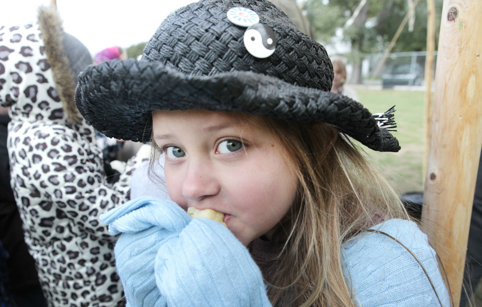 Photo - Fourth-grader Marie Thille eats a biscuit from the Oklahoma History Center chuckwagon.