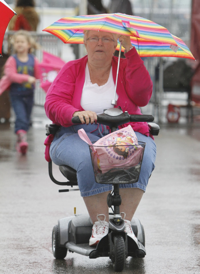 Photo - Betty Beavers uses her umbrella during opening day of the Oklahoma State Fair at State Fair Park in Oklahoma City, Thursday  September  13, 2012. Photo By Steve Gooch, The Oklahoman