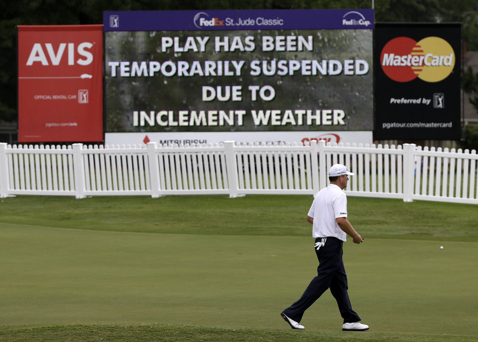 Photo - A golfer heads to the clubhouse during a weather delay at the second round of the St. Jude Classic golf tournament Friday, June 6, 2014, in Memphis, Tenn. (AP Photo/Mark Humphrey)