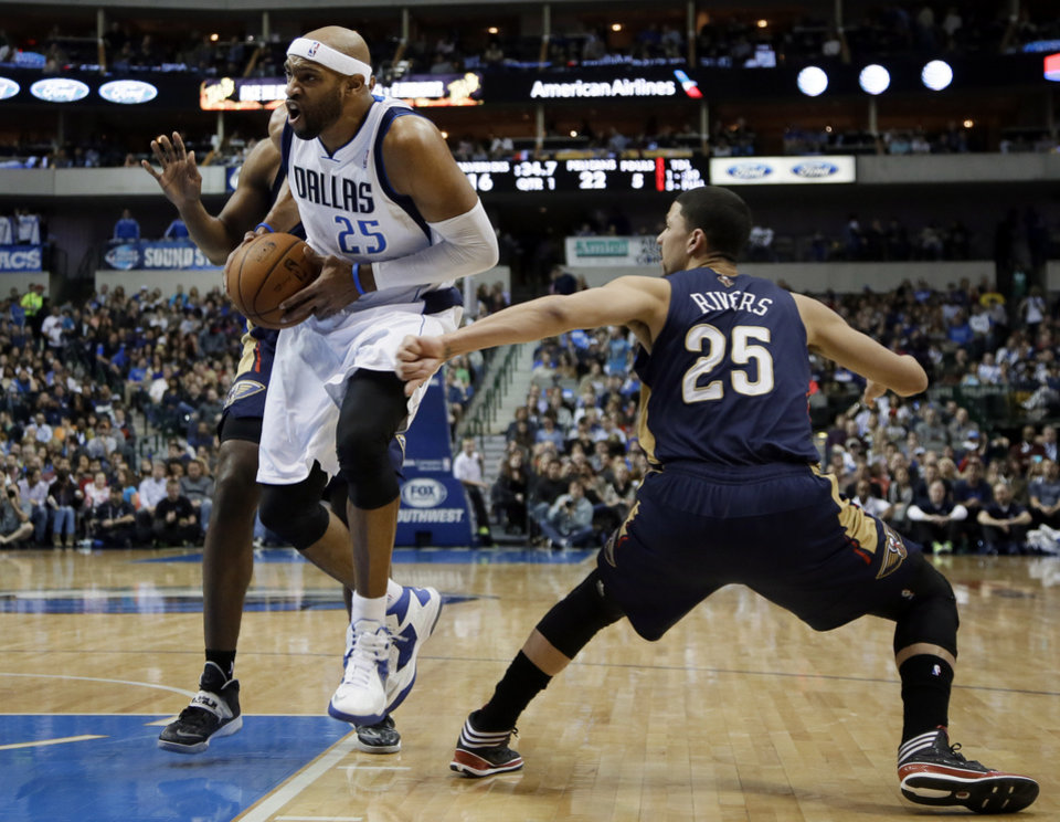 Photo - Dallas Mavericks' Vince Carter (25) drives past New Orleans Pelicans' Anthony Morrow, rear, and Austin Rivers (25) on his way to the basket during the first half of an NBA basketball game, Saturday, Jan. 11, 2014, in Dallas. (AP Photo/Tony Gutierrez)