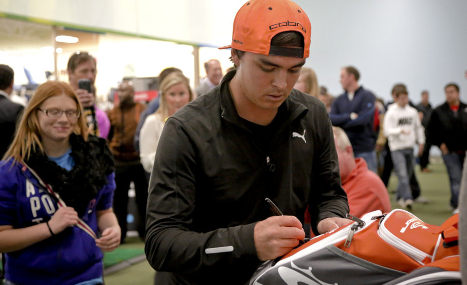 Photo - Former Oklahoma State golfer and current PGA pro Rickie Fowler signs autographs on golf bags while making a special appearance at Golfsmith in Oklahoma City, Okla. as a surprise to members for the three Moore school's golf teams, Monday, Jan. 6, 2014.  .Photo by Chris Landsberger, The Oklahoman