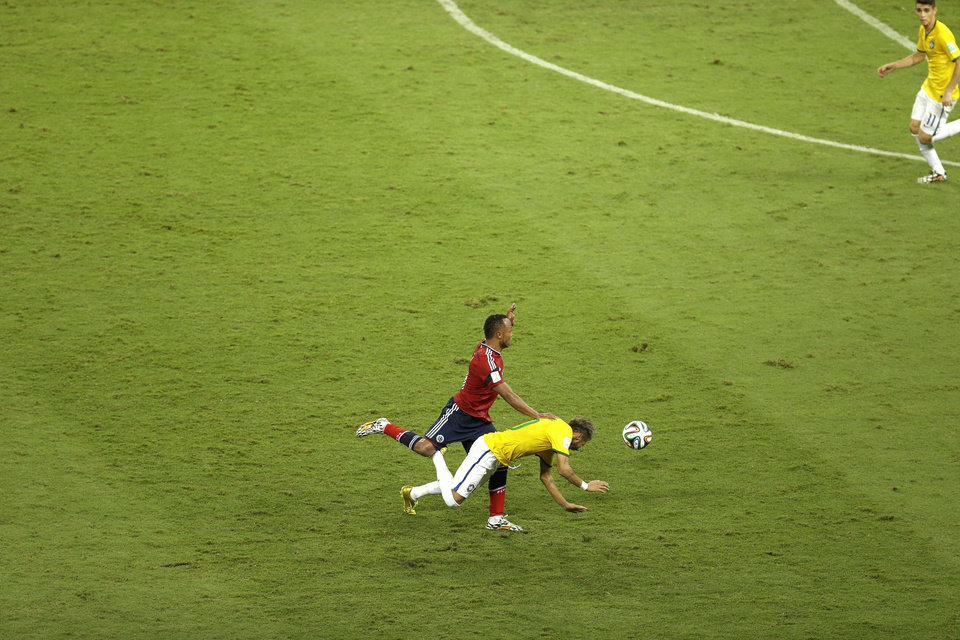 Photo - Brazil's Neymar, bottom, falls beside Colombia's Juan Zuniga during the World Cup quarterfinal soccer match between Brazil and Colombia at the Arena Castelao in Fortaleza, Brazil, Friday, July 4, 2014. (AP Photo/Themba Hadebe)