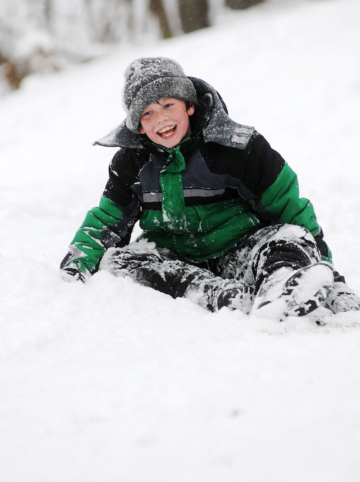 Photo - Daniel Meier, 11 of Winona, Minn., laughs after falling in the snow while sledding down the hill at Bluffside Park Thursday, Dec. 20, 2012, in Winona, Minn. (AP Photo/Winona Daily News, Joe Ahlquist)