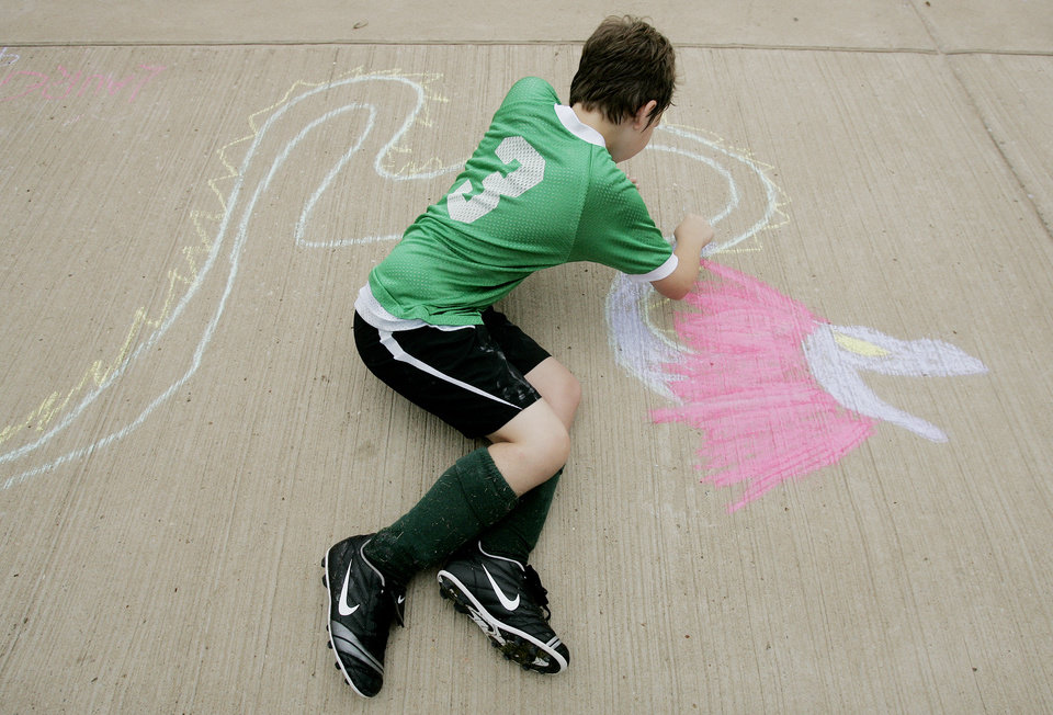 Lauren Grissom ,9, of Noble draws a dragon during the Cleveland county CROP walk to stop hunger Sidewalk Chalk Art contest for Kids and Families Saturday, Sept. 13, at the Santa Fe Depot in Norman,OK. BY JACONNA AGUIRRE, THE OKLAHOMAN