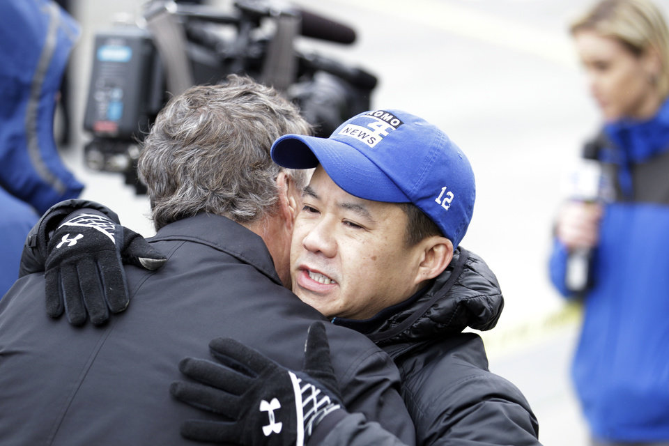 Photo - KOMO assignment editor Norm Mah, right, gets a hug as he works at the scene of the crash of a KOMO news helicopter Tuesday, March 18, 2014, in Seattle. A KOMO-TV helicopter helicopter crashed into a city street near Seattle's Space Needle on Tuesday, killing two people and critically injuring a person in a car on the ground. (AP Photo/Stephen Brashear)