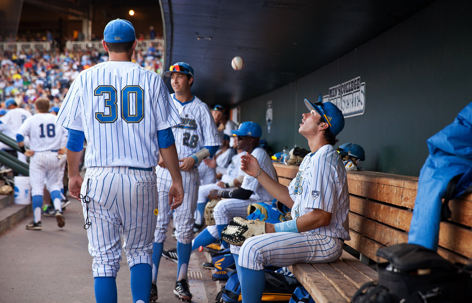 Photo - UCLA's Christoph Bono (3), right, tosses a ball in the dugout while waiting for Game 12 against North Carolina during the College World Series at TD Ameritrade Park in Omaha, Neb., Friday, June 21, 2013. (AP Photo/The Omaha World-Herald/Alyssa Schukar) MAGAZINES OUT; ALL LOCAL TV OUT