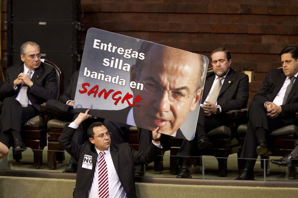 A member of Mexico\'s National Congress holds a poster with an image of outgoing President Felipe Calderon that reads in Spanish: