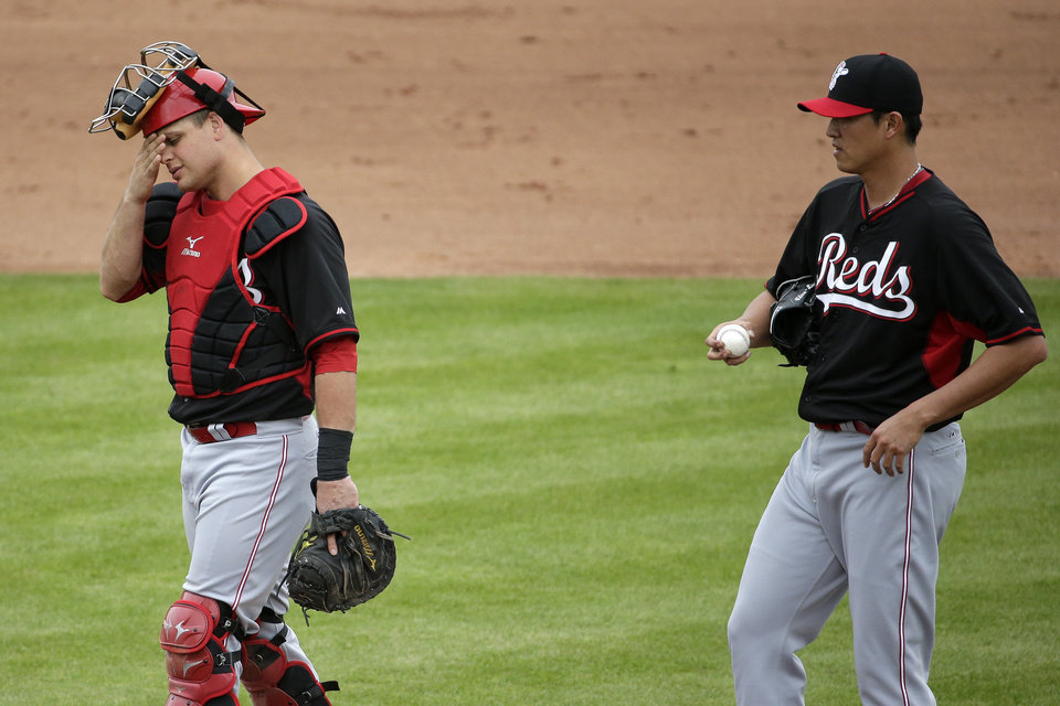 Photo - Cincinnati Reds catcher Devin Mesoraco, left, wipes his face after talking with pitcher Chien-Ming Wong, who gave up three runs to the San Francisco Giants during the fifth inning of a spring training baseball game in Scottsdale, Ariz., Thursday, March 6, 2014. (AP Photo/Chris Carlson)