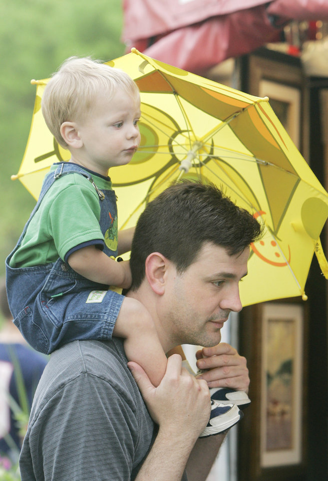 Eric Jones carries his son Jackson Jones, 1, who holds his umbrella, during their visit to the Festival of the Arts Wed. April 23, 2008 in downtown Oklahoma City, OK. BY JACONNA AGUIRRE/THE OKLAHOMAN.