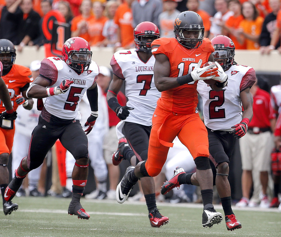 Oklahoma State\'s Blake Jackson (18) outruns Louisiana-Lafayette\'s Darius Barksdale (5), Delvin Jones (7) and Jemarlous Moten (2) during a college football game between Oklahoma State University (OSU) and the University of Louisiana-Lafayette (ULL) at Boone Pickens Stadium in Stillwater, Okla., Saturday, Sept. 15, 2012. Photo by Sarah Phipps, The Oklahoman