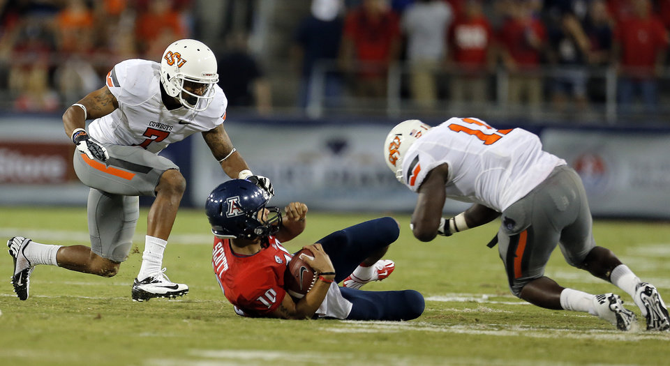 Photo - Oklahoma State's Shamiel Gary (7) and Shaun Lewis (11) tackle Arizona's Matt Scott (10) during the college football game between the University  of Arizona and Oklahoma State University at Arizona Stadium in Tucson, Ariz.,  Saturday, Sept. 8, 2012. Photo by Sarah Phipps, The Oklahoman