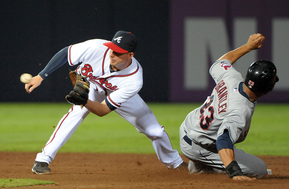 Photo - Cleveland Indians' Michael Brantley (23) safely steals second base in front of Atlanta Braves second baseman Elliot Johnson during the sixth inning of a baseball game at Turner Field, Tuesday, Aug. 27, 2013, in Atlanta. (AP Photo/David Tulis)