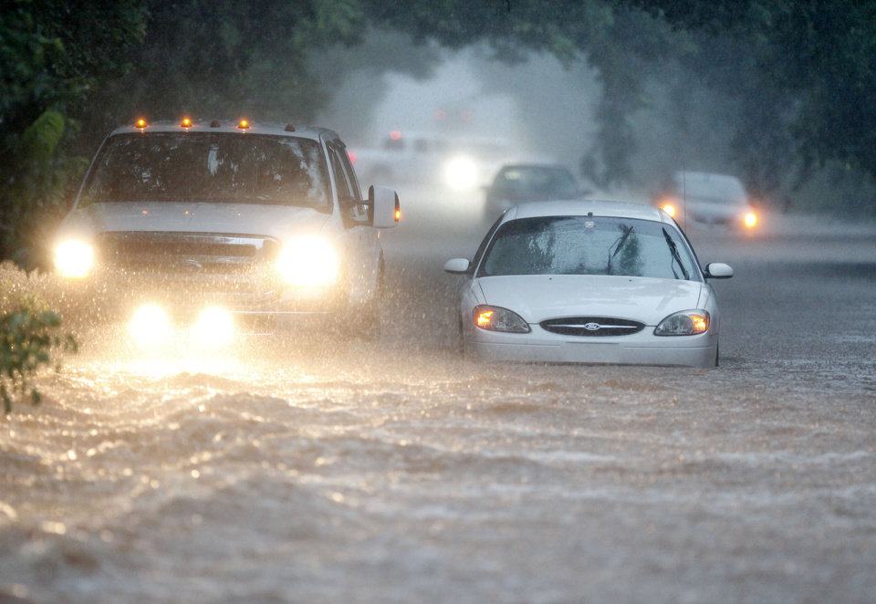Photo - The driver of a pickup truck attempts to help a stranded motorist whose car stalled in deep floodwaters on Kelly Avenue between Hefner and 122nd in Oklahoma City, OK, Monday, June 14, 2010. By Paul Hellstern, The Oklahoman