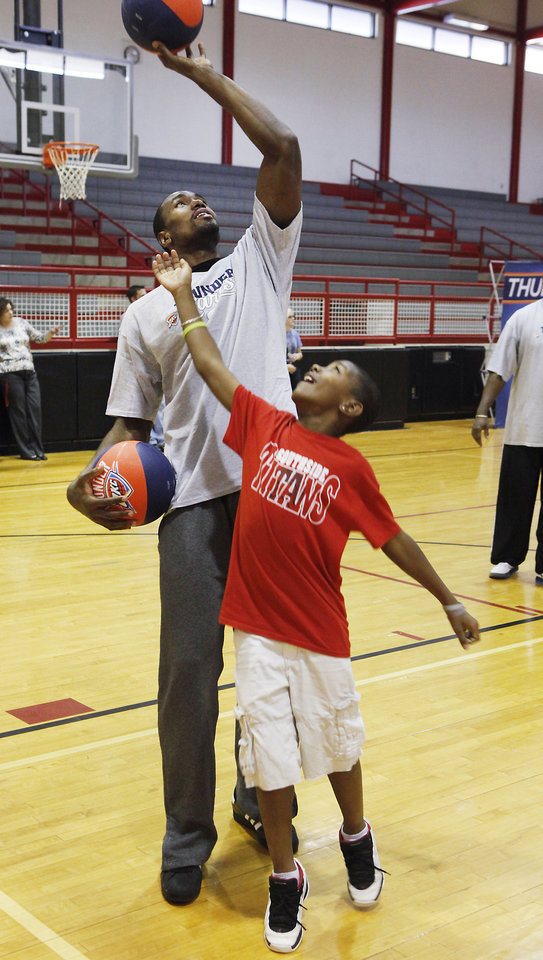 Sixth-grader Amar Johnson tries to get the ball from Thunder player Serge Ibaka   during a lesson at Cimarron Middle School in Edmond Thursday. PHOTO BY DAVID MCDANIEL, THE OKLAHOMAN <strong>David McDaniel - The Oklahoman</strong>