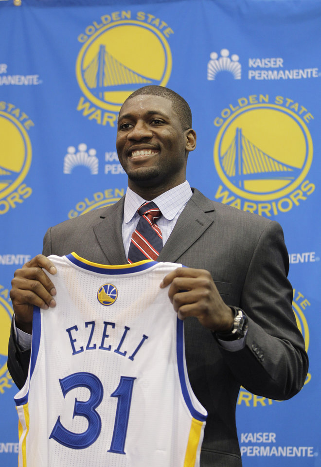 Golden State Warriors second draft pick Festus Ezeli, a center from Vanderbilt, holds up his new jersey during a news conference at Warriors headquarters in Oakland, Calif., Monday, July 2, 2012. (AP Photo/Paul Sakuma)