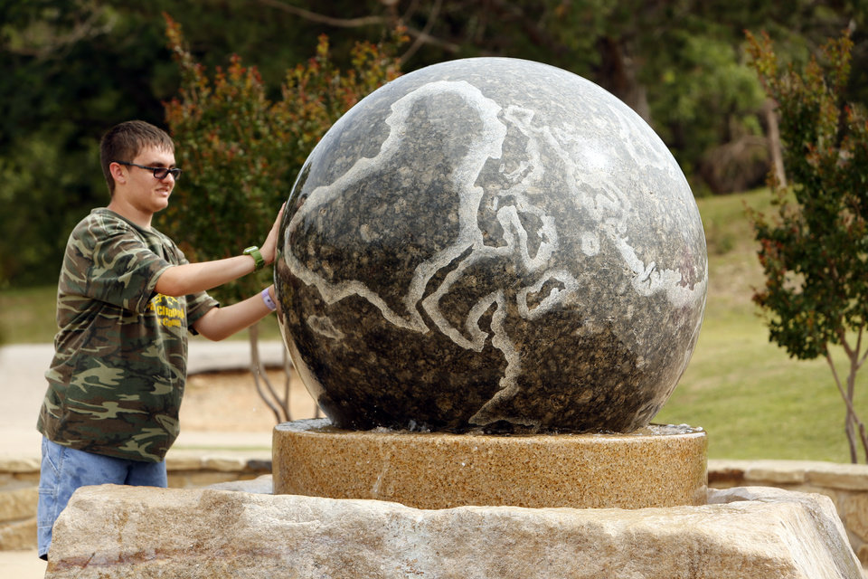 Jahue Underwood, 14 from Wichita Falls, spinns a solid marble globe suspended on a water filled bearing at a missions display at Falls Creek Youth Camp on Tuesday, June 25, 2013 in Davis, Okla.  Photo by Steve Sisney, The Oklahoman