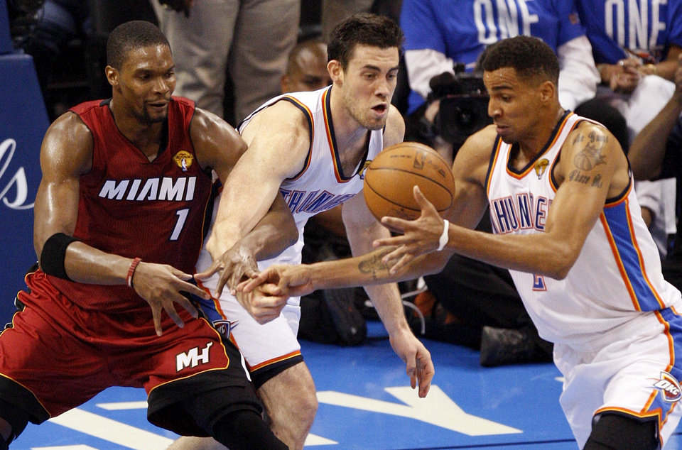 Oklahoma City's Nick Collison (4), middle, and Thabo Sefolosha (2) take the ball from Miami's Chris Bosh (1) in the fourth quarter during Game 1 of the NBA Finals between the Oklahoma City Thunder and the Miami Heat at Chesapeake Energy Arena in Oklahoma City, Tuesday, June 12, 2012. Oklahoma City won, 105-94. Photo by Nate Billings, The Oklahoman
